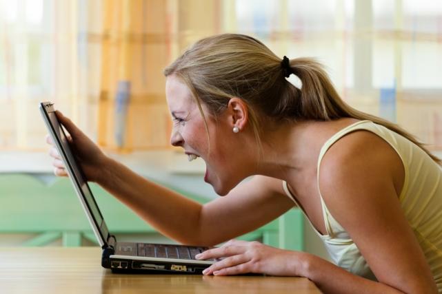 Eine Frau ärgert sich über Ihren Computer. Probleme mit Hardware, Software und Internetshopping