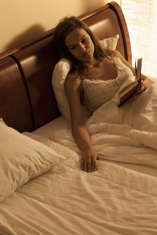 Young woman lying in bed, suffering from loneliness