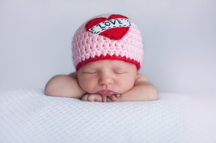 """Portrait of a seven day old sleeping baby girl wearing a crocheted """"Love"""" beanie. Cute shot to use for Valentine's Day."""